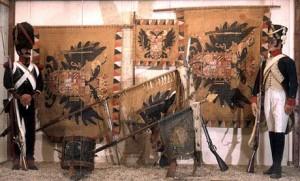 Dieses Bild zeigt österreichische Standarten und Fahnen, die im Feldzug 1805 in Ulm und Austerlitz von den Österreichern erbeutet wurden. Links wird ein Sergent der Karabiniers vom 8ème Régiment d'infanterie Légère (1806-1810) gezeigt - rechts befindet sich ein Füsilier vom 8ème Régiment d'infanterie de Ligne (1808-1812). Quelle: Musée de l'Empéri de Salon-de-Provence (collections du Musée de l'Armée)